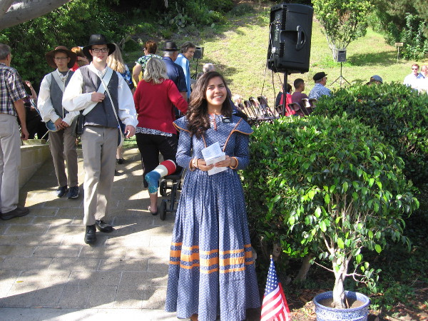 A friendly Mormon lady in pioneer dress welcomes guests to the Flag Day Celebration.