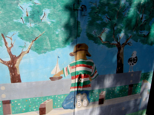 One side of a utility box shows the back of a young boy playing on a bench with a toy boat.