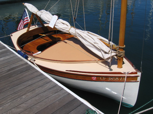 This small boat is named Tom. It's a 2015 catboat. Carvel planked Port Oxford cedar on white oak frames.