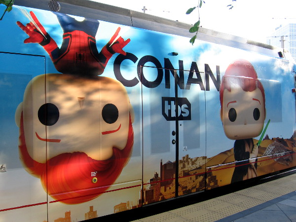 Conan is hanging upside down from the roof of the trolley. He is your friendly neighborhood Spiderman!