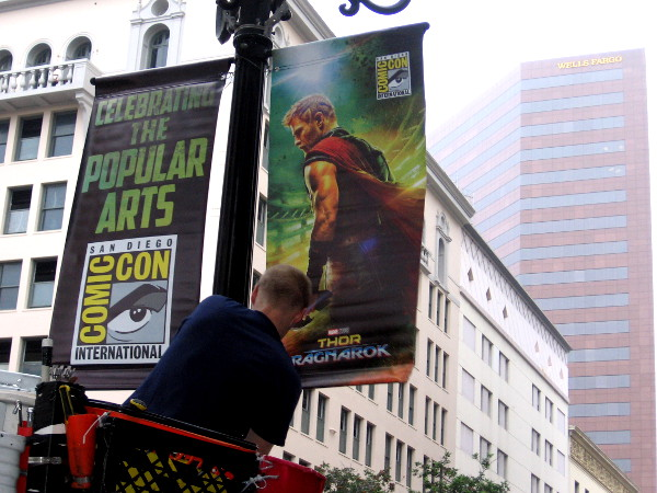 Workers hang San Diego Comic-Con banners along Fifth Avenue in the Gaslamp Quarter.