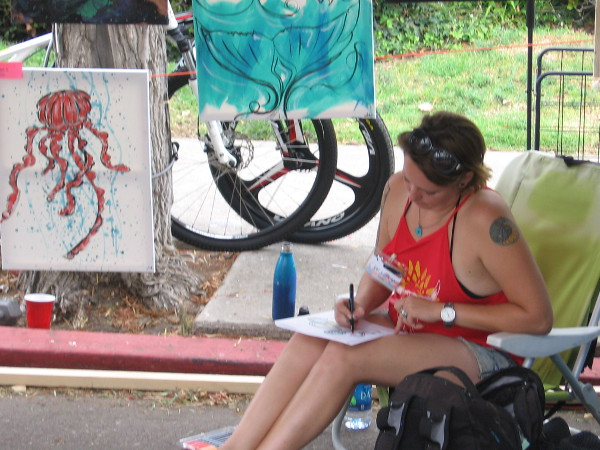 Another artist at the Ocean Beach Street Fair concentrates on her work.
