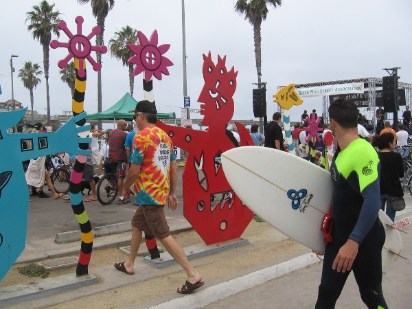 Some surfers pass fun public art on Newport Avenue. They hear music coming from the main stage by the beach.