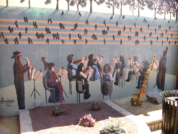 One mural behind a small succulent garden shows musicians in a public concert.