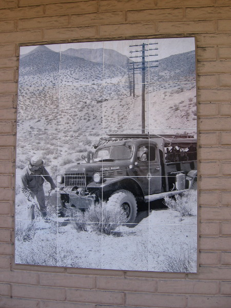 Old photo on ATT building shows telephone company worker in the undeveloped hills of La Mesa many years ago.