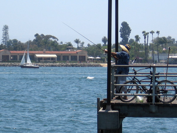 Fisherman on pier and a sailboat.