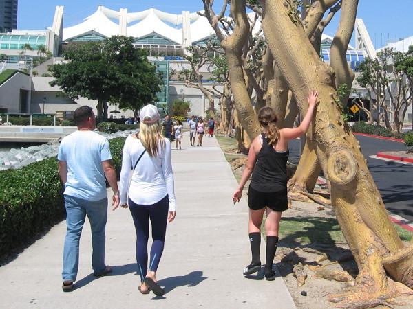 Walking along, touching a tree.