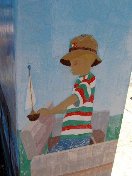 One side of the same box. We now see the side of the boy who is holding his boat.