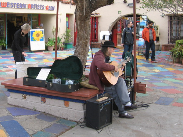 A musician strums in Spanish Village.
