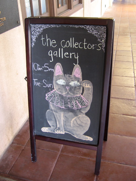 A chalk cat in Balboa Park waves to passing visitors. Fun art outside the Mingei Museum's Collectors Gallery.