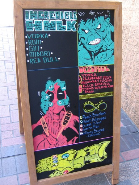 Funny sign on downtown San Diego sidewalk depicts Hulk squeezing Deadpool's head and the Infinity Gauntlet.