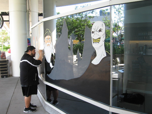 Artist paints Harry Potter characters in windows of the Hilton Bayfront Starbucks.