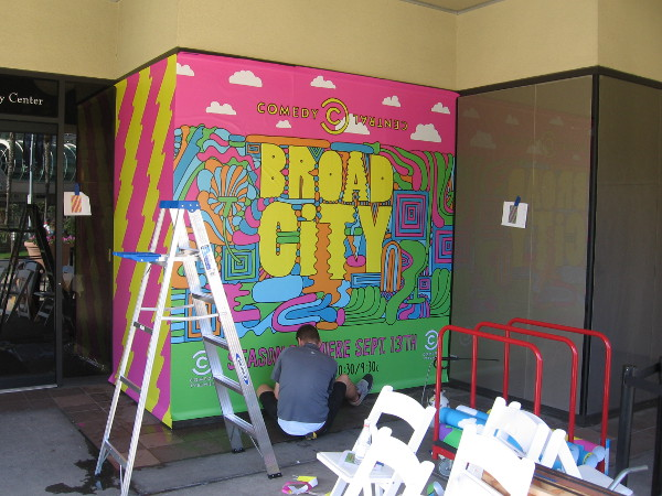 Someone paints a graphic along MLK Promenade promoting Broad City on Comedy Central.