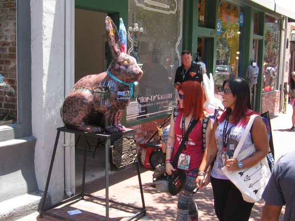"People attending 2017 San Diego Comic-Con look at an artfully painted rabbit outside the Rabbitville ""Hop-Up"" Gallery."