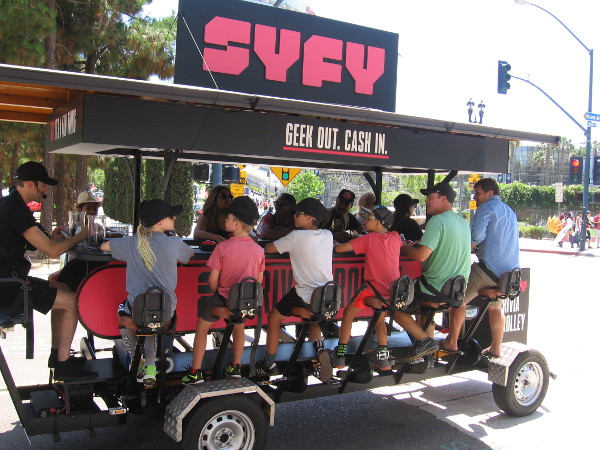 People peddle the Syfy Trivia Trolley while answering questions for prizes!
