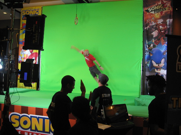 The Sonic the Hedgehog booth had people jump for a ring in front of a green screen for prizes. They could see themselves in a video game.