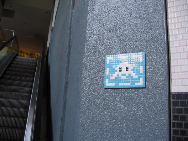 A space invader made of tile near a Horton Plaza escalator!