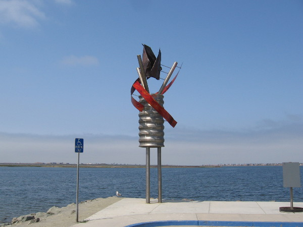 An unusual sculpture. Powering the Arts, by artist Micheal Leaf, 2015. It stands next to the blue water in Chula Vista Bayfront Park.