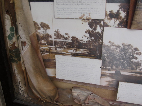 Decayed flag and old photos of tall flagpole at center of La Plaza de Las Armas.