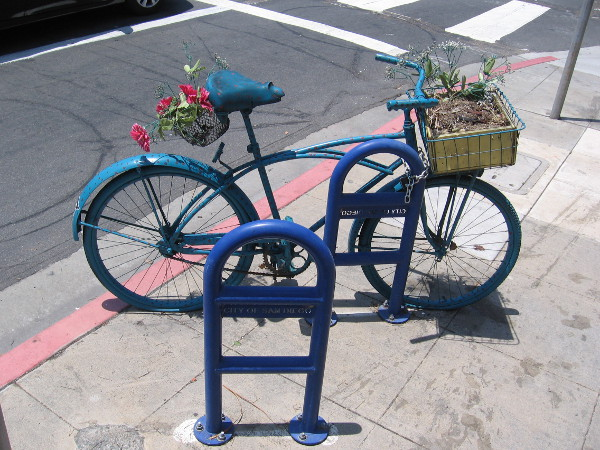 Someone's artistic bicycle has a potted plant in its basket.
