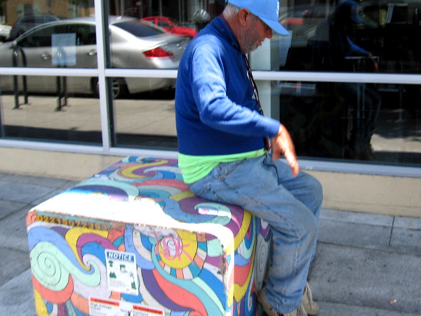 Someone rests on a painted transformer box on Adams Avenue near 30th Street.