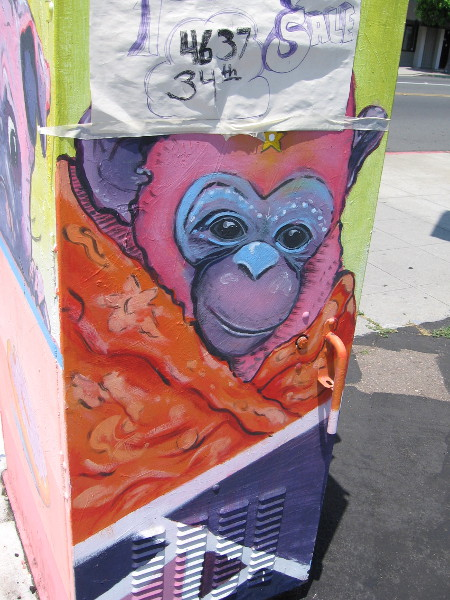 A monkey on a utility box, crowned by a rummage sale notice.