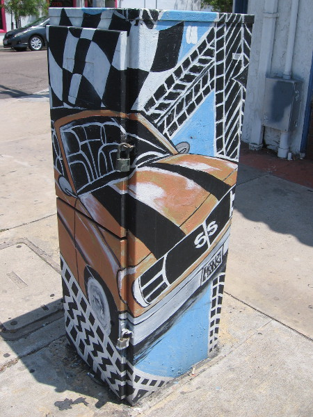A classic car and tire tracks painted on a utility box on the sidewalk in front of Tire Depot.
