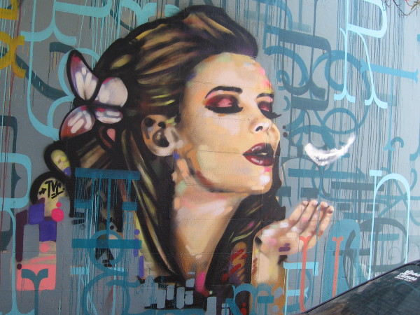A beautiful female face and a blown feather. If you know who this mural represents, leave a comment!