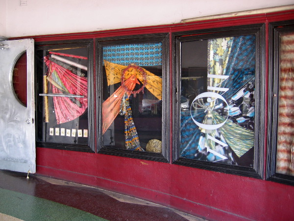 Fabric art in windows of the old theater, where movie posters were once displayed.