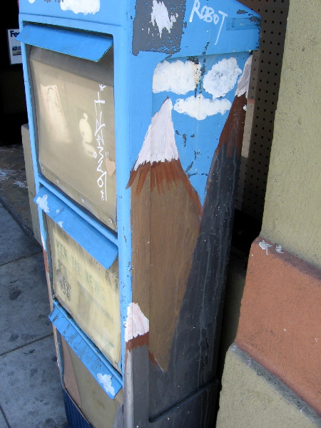 A snow-capped mountain peak on the side of a newspaper box.