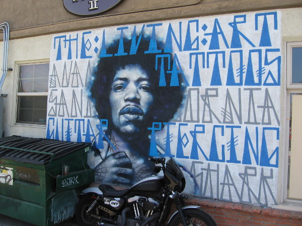 An awesome Jimi Hendrix street mural near dumpster and motorcycle.
