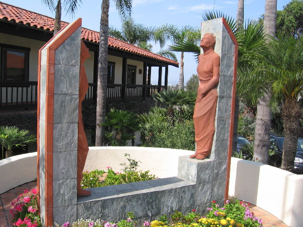 Two terracotta female figures stand at corner of Heritage Plaza, near the intersection of San Diego Avenue and Hortensia Street.