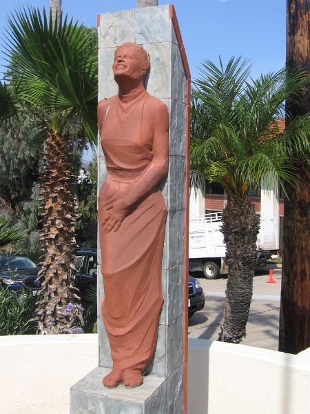 Graceful female figure sculpted with lifted head and smile.