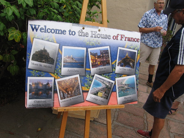 A poster says Welcome to the House of France. It depicts Mont St. Michel, Château de Versailles, la Tour Eiffel, and other popular national attractions.