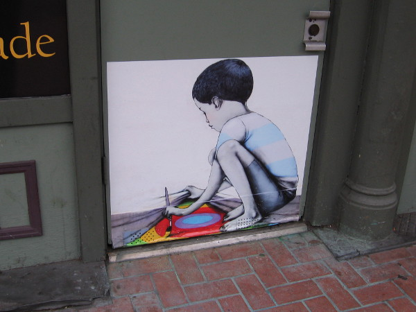 Street art in the Gaslamp shows child making a secret painting.