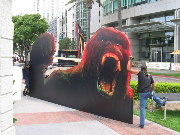 King Kong is so enraged it takes two sturdy workers to hold him at bay! I hope the movie ape doesn't escape and go on a rampage during Comic-Con!