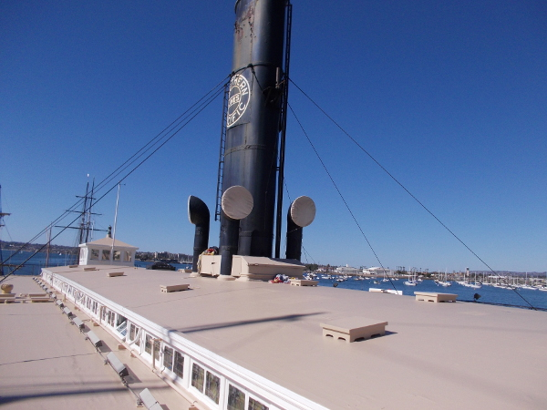 Photo over the roof of the ferryboat, with a black funnel projecting into the blue San Diego sky.