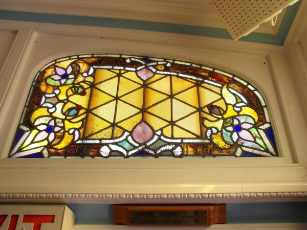 Different stained glass windows on the ship infuse the passenger deck with colored light.