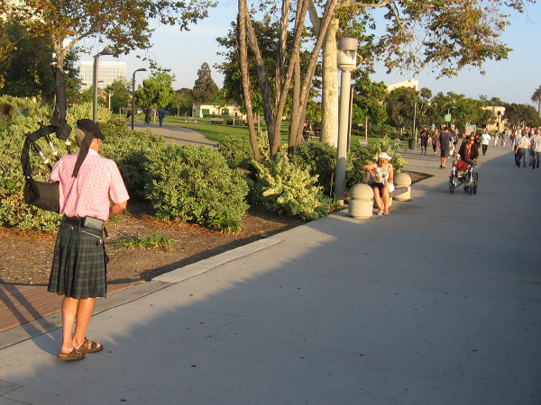 Walking very slowly, rhythmically, toward Ruocco Park, playing bagpipes.