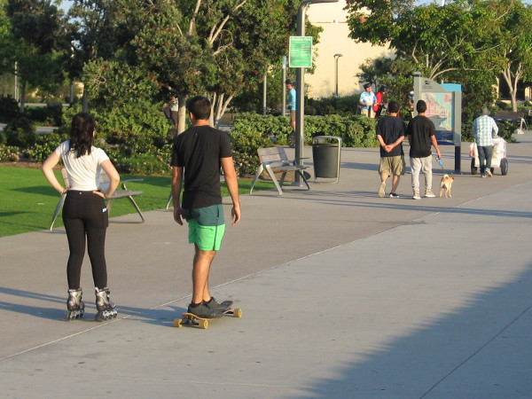 Couple rolls down the Embarcadero on inline skates and a skateboard.