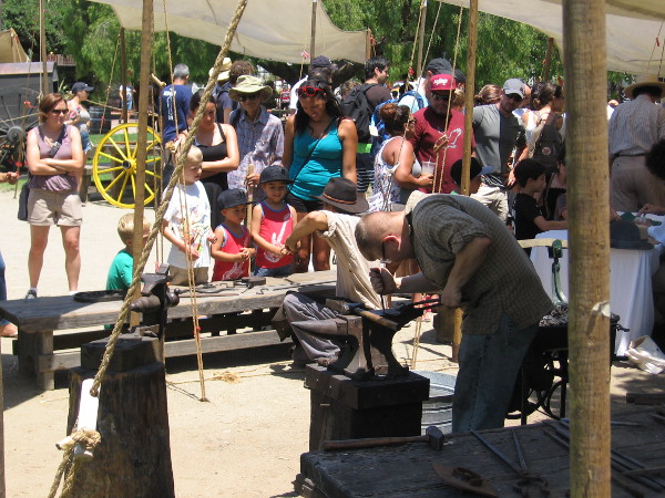 Young and old alike watched two blacksmiths at work with an anvil and small portable forge.