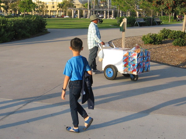 Kid looks with yearning at an ice cream seller's cart.