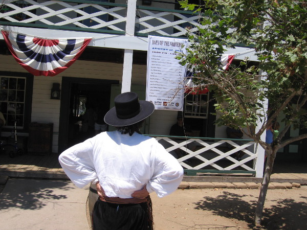 Someone reads Days of the Vaqueros sign on the Robinson Rose House in Old Town San Diego State Historic Park.