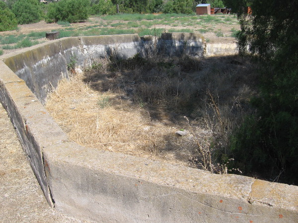 An octagonal concrete reservoir to the north, uphill from the ranch house. Photographic evidence shows water might have been pumped up here by windmill.