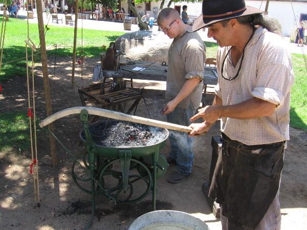 This portable green forge is being used for the first time. The handle turns a belt which operates an air blower. I recognized this blacksmith from the Fall Back Festival in San Diego's Gaslamp Quarter.