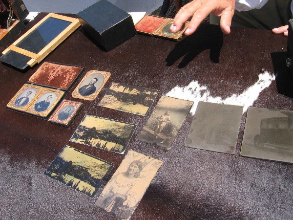 A gentleman had a table containing old tintype photographs. He also had antique cameras on display that produce daguerreotype photographs.