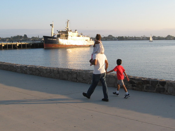 A family walks along and gazes out at a sunlit ship.