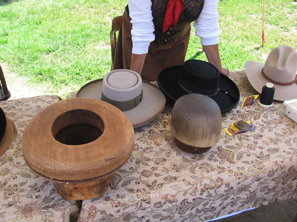 A hat maker shows how beaver felt material was steamed then pushed over a hat-form block.