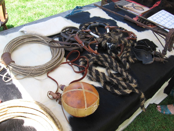 On this table I see more ropes, a canteen, iron brands and boot spurs.