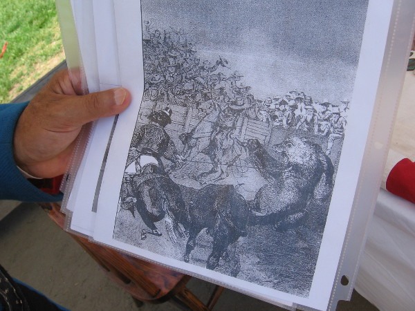 A gentleman who teaches students visiting Old Town about history holds up an illustration of bear-baiting, which early Californians found entertaining.